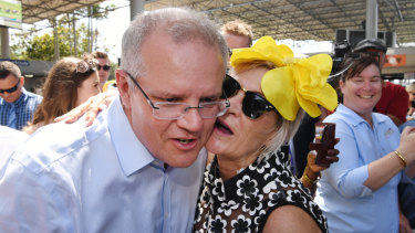 The Prime Minister is kissed by a racegoer on Melbourne Cup Day at the Corbould Park Racecourse at the Sunshine Coast.