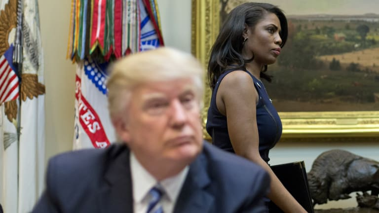 Omarosa Manigault Newman, formerly the director of communications for the Office of Public Liaison, walks past President Donald Trump during a March, 2017 meeting.