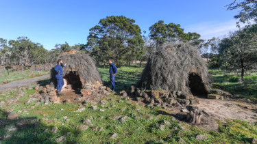 Budj Bim rangers Aaron Morgan and Leigh Boyer stand by replica stone houses.