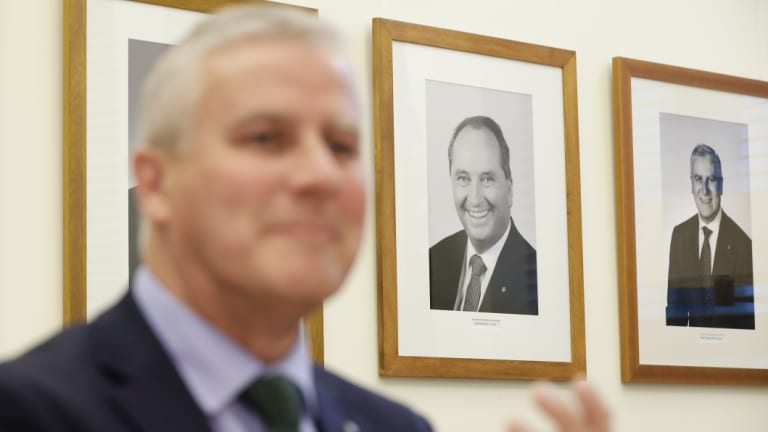 A portrait of former Nationals leader Barnaby Joyce hangs on the wall behind Deputy Prime Minister Michael McCormack. The new party leader has defended the Coalition's commitment to decentralisation.