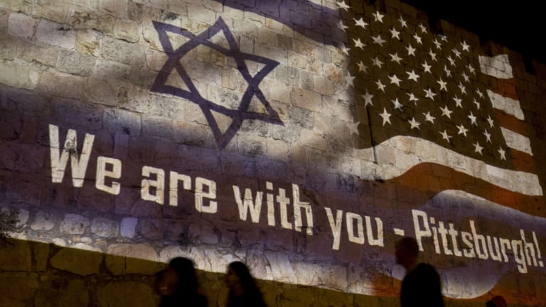 People walk past a projection on the Old City wall in Jerusalem on Sunday in a commemoration of the victims of a deadly shooting at a Pittsburgh synagogue.