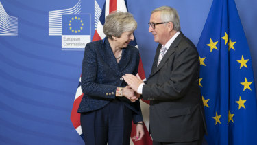 Theresa May, left, shakes hands with Jean-Claude Juncker, president of the European Commission, during a meeting in Brussels on Saturday.