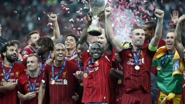 Liverpool's Sadio Mane raises the trophy to celebrate with teammates after winning the UEFA Super Cup.