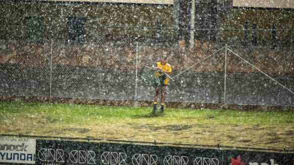 A lone spectator packs up his chair in the rain at Seiffert Oval on Thursday night.