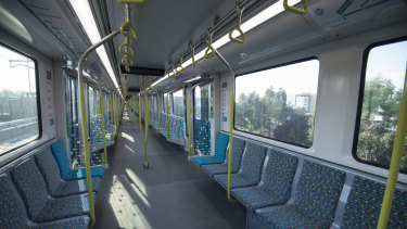 A single-deck metro train speeds along the line from Rouse Hill.