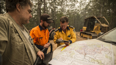 Property owners Brad Edge, Ben Donnelly and Anthony Roberts from the RFS discuss the fire map ahead of worsening weather conditions.