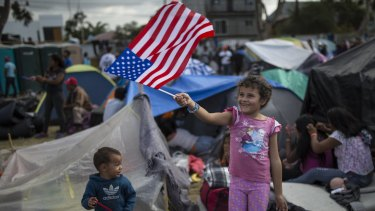 Seven-year-old Honduran migrant Genesis Belen Mejia Flores waves an American flag at US border control helicopters flying overhead near the Benito Juarez Sports Centre serving as a temporary shelter for Central American migrants, in Tijuana, Mexico, on Saturday.