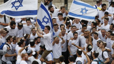 Israeli youths wave national flags outside the Old City's Damascus Gate.