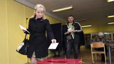 A Latvian woman casts her ballot papers at a polling station in Riga, Latvia, on Saturday.