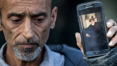 Omar Nabi, Yama's brother, holds a photo of their father, 71 year old Haji Daoud who was killed in the Masjid Al Noor Mosque in Christchurch.