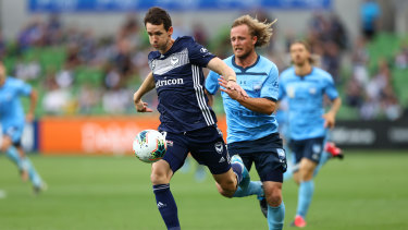 Full steam ahead: Victory striker Robbie Kruse surges forward as Sydney's Rhys Grant gives chase.