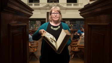 Rare book historian Dr Anna Welch with one the books that had images cut out of it.