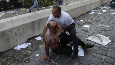 A man helps an injured person near the blast site in Beirut.