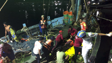 Rescued tourists from a boat that sank are helped onto a pier from a fishing boat in Phuket.