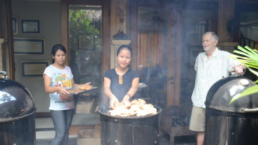 Bubba with his two employees, Ayu (left) and Sasa (centre), loading four chickens onto his Weber Smoky Mountain smoker.