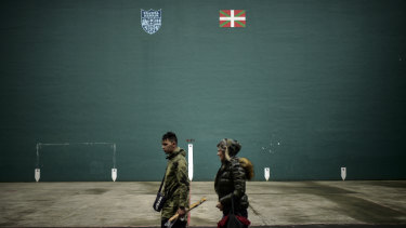 A couple walk past beside a wall painted with the Basque flag, or Ikurrina, top right, and the symbol of the Basque Country, in the small in the small basque village of Hernani, northern Spain.