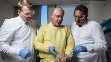 Michael Buckland of RPA, Chris Nowinski from Concussion Legacy Foundation and former rugby player Colin Scotts examine a brain.