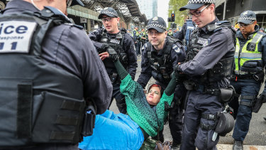 An Extinction Rebellion protester is stopped by police on Thursday.