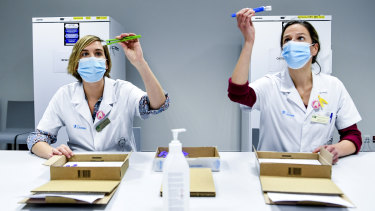 Health workers in Belgium inspect vials of the Pfizer-BioNTech coronavirus COVID-19 vaccine, which is one of the candidates expected to receive approval in Australia by the end of January.