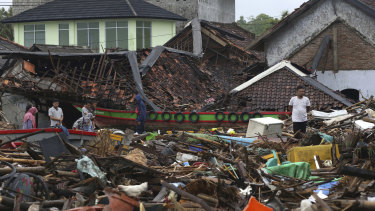 People inspect the damage at a tsunami-ravaged village in Sumur, Indonesia, on Christmas Day.