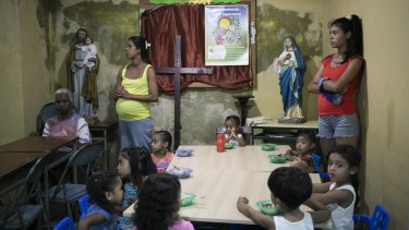 Children eat at a soup kitchen as adults wait to be served in the Petare slum, in Caracas, Venezuela, last week.