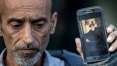 Omar Nabi, brother of Yama, holds a photo of his father Haji Daoud, who was killed in the attack.