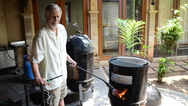 "Ronald Craig Flint, widely known as Bubba, uses his ""Texas torch"" to get his barbecue started to smoke four chickens."