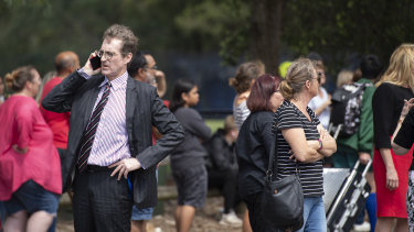 Parents and staff wait outside Epping Boys High School for a group of year nine boys to return from camp on Friday.