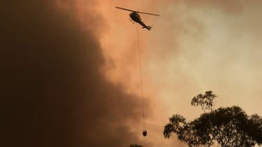 A helicopter circles overhead near Yanderra Road as the Green Wattle Creek Fire approaches Yanderra.
