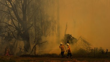 NSW RFS fire fighters surrounded by smoke as they work on battling a fire at Tahmoor, NSW.