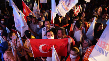 Supporters of the newly elected Turkish Cypriot leader Ersin Tatar hold a Turkish flag in the Turkish occupied area in the north part of the divided capital Nicosia after the election.