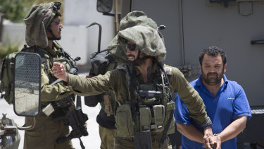 Israeli soldiers make one of several arrests of Palestinians last month after a soldier was killed by a rock thrown from a rooftop in the West Bank village of Yabad.