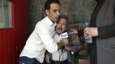 A man cries at a hospital after he lost his journalist son in an explosion in Kabul.