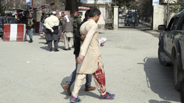 An injured man is assisted to hospital after three explosions struck a Shiite shrine in Kabul.
