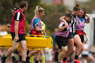 Magpie Brianna Davey leaves the field injured.