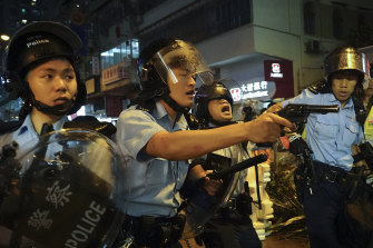 Police officers draw their weapons during a confrontation with protesters in Hong Kong on Sunday.