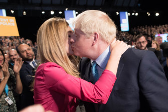 The Prime Minister exits the hall with his girlfriend Carrie Symonds following his keynote speech.
