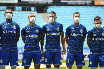 Gremio players take to the field in masks.