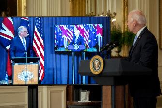 US President Joe Biden listens as Prime Minister Scott Morrison speaks via videoconference in the East Room of the White House.