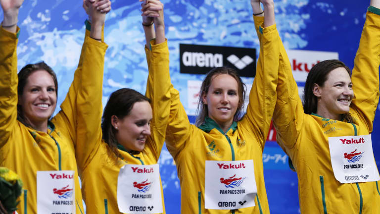 The Australian team celebrate on the podium after winning the women's 4x100m medley relay final.