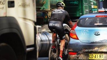 A cyclist in traffic in the Sydney CBD.