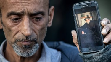 Omar Nabi holds a photo of his father Haji Daoud, who was killed in the attack.