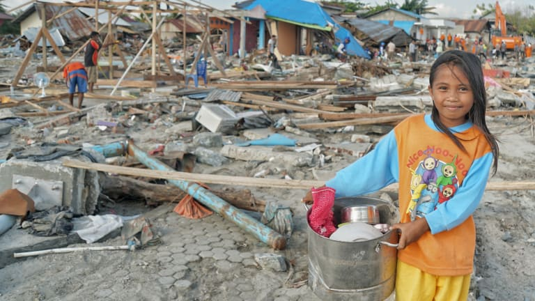 Ten-year-old Suci Rahmadi at Mamboro beach with pots and pans  she has collected from the debris.