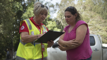 Courier driver Sophie Bryden (right), 38, speaks to Red Cross workers at Canungra Sports and Recreation Ground.