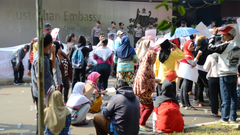 Protesters, some of whom were paid to attend, sit around bored at a rally outside the Australian embassy in Jakarta.