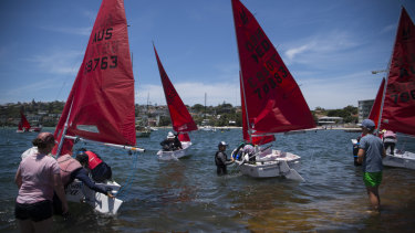 Mirror Dinghy class sailing boats launch before a race on Sydney Harbour.