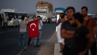 People wave Turkish flags in support of Turkish soldiers crossing the border into Syria.