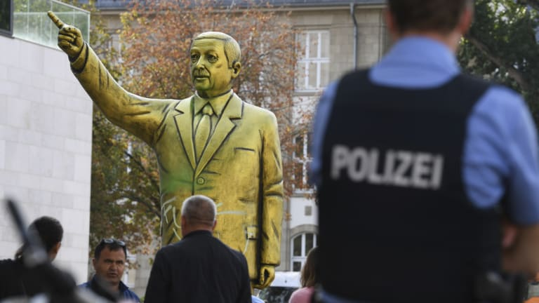 Police and passersby surround a statue showing Turkish President Erdogan which is part of the art festival  'Wiesbaden Biennale' in Wiesbaden, western Germany.