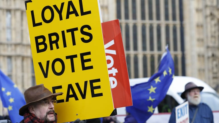 A vote leave pro-Brexit demonstrator holds a placard with anti Brexit protesters in the background as they voice their opinions outside the Palace of Westminster, in London.