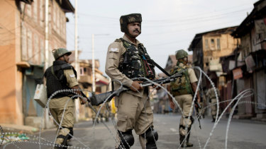 Indian paramilitary soldiers stand guard during curfew in Srinagar on August 7.